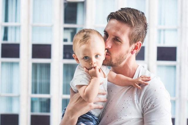 Muž v bielom tričku bozkáva malé dieťa na líce.jpg