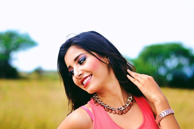Žena v oranžovom tričku s výrazným náhrdelníkom a náramkom stojí na rozkvytnutom poli