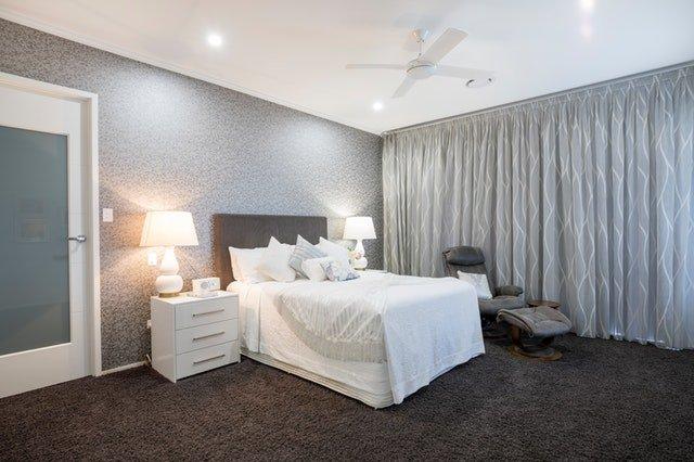 Spálňa so sivým závesom a veľkou posteľou
