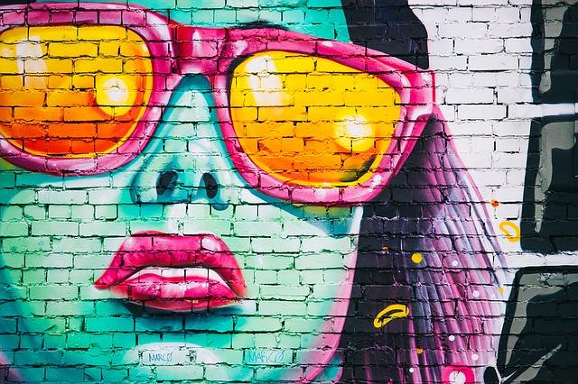 Farebná ženská tvár s okuliarmi namaľovaná na tehlovej stene.jpg
