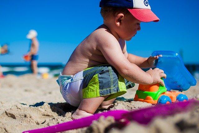 Dieťa sa hrá na pláži s formičkami v piesku.jpg