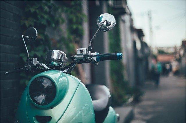 Tyrkysová motorka na ulici pri tehlovom múre