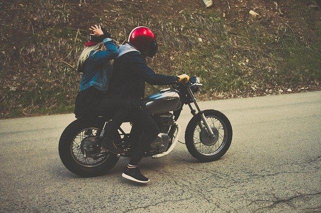 Chlapec a dievča s červenými prilbami na motorke
