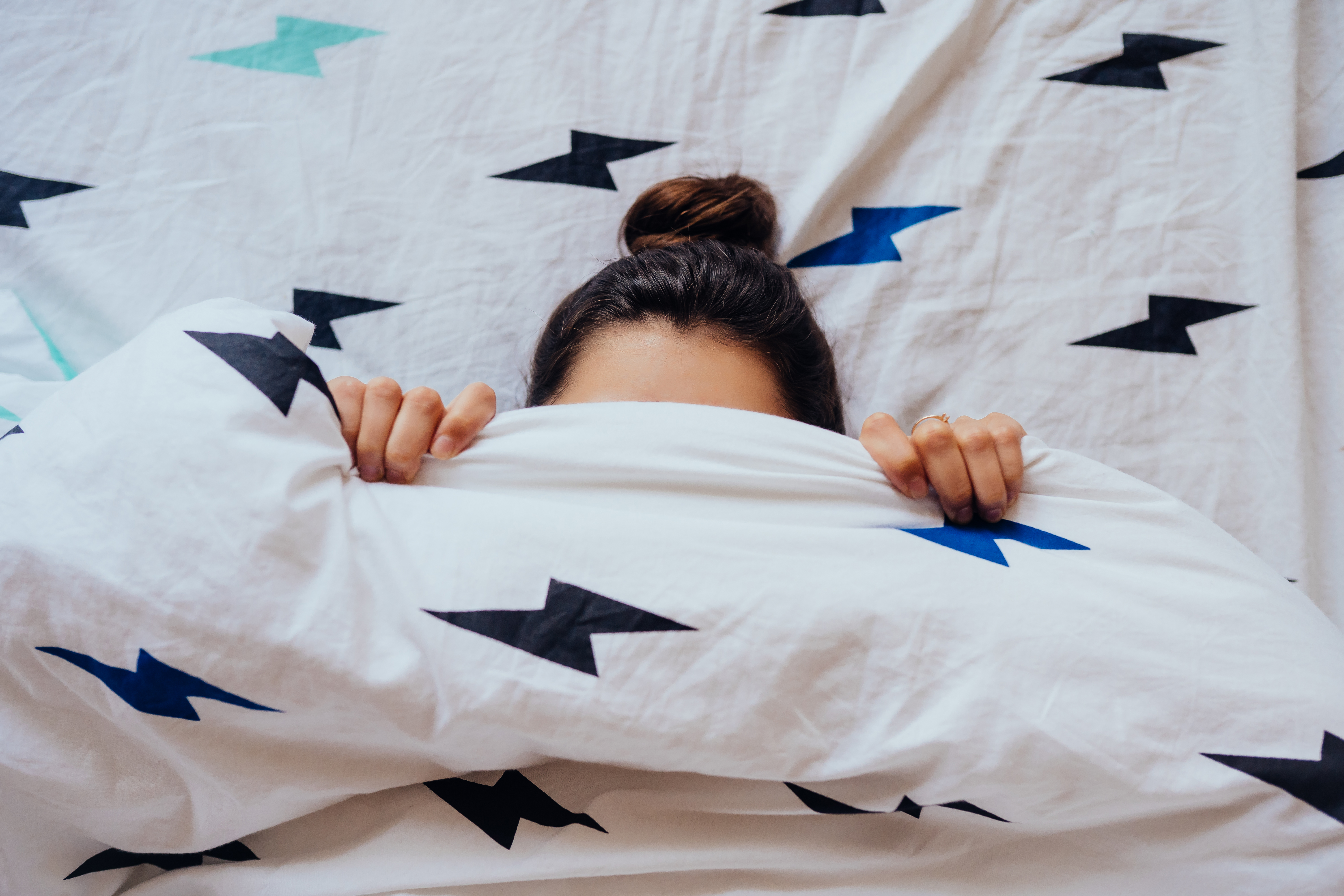 lovely-young-woman-lies-bed-covered-with-blanket