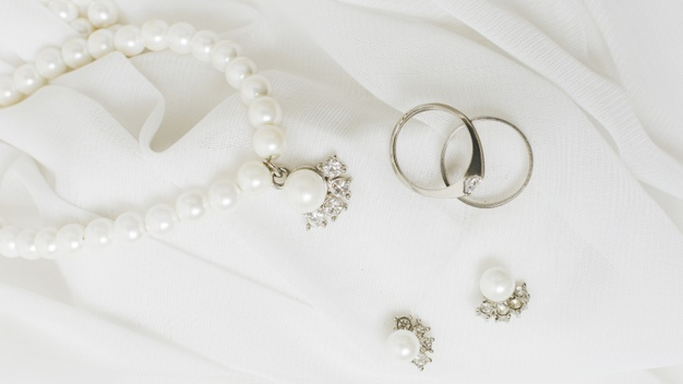 silver-wedding-rings-earrings-pearl-necklace-white-lace_23-2148187562